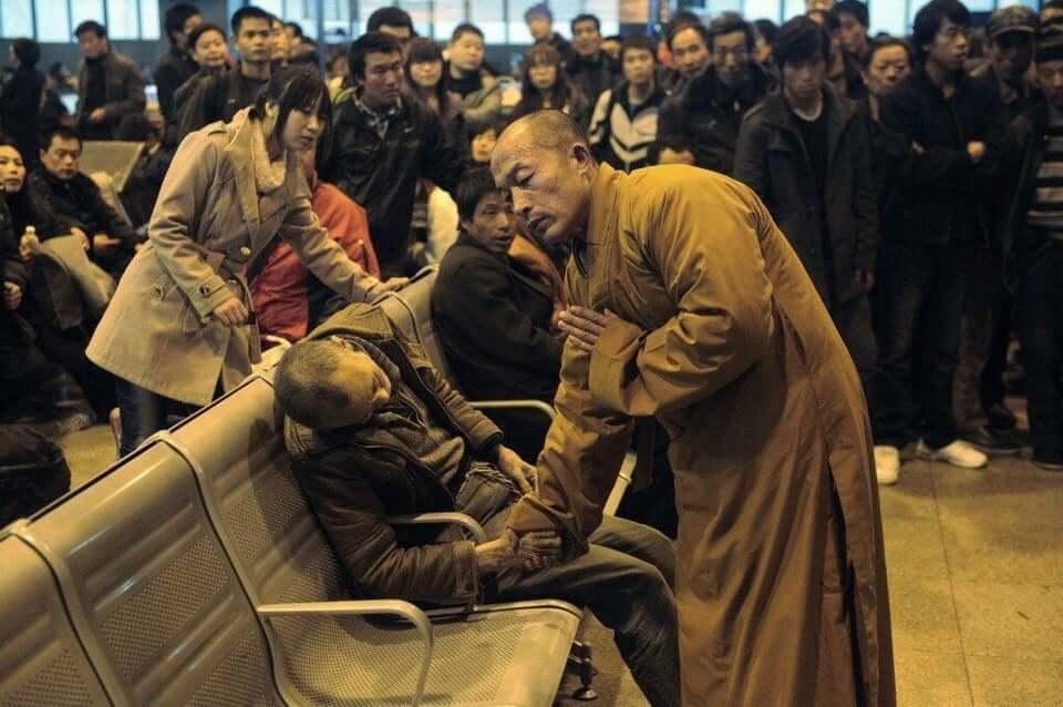 A munk prays for a deceased man (Shanxi Taiyuan train station, China)