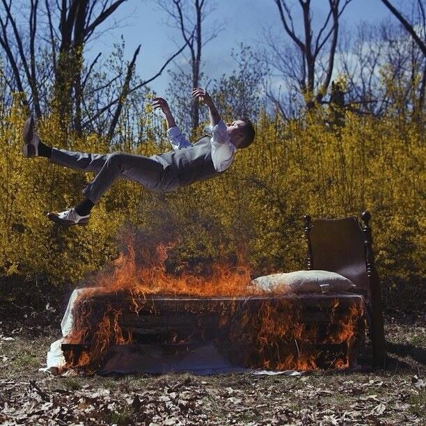 Man falling onto burning bed